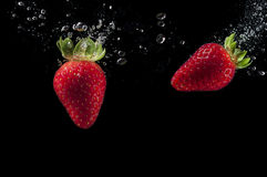 Wirkliches frische Frucht trawberries Spritzen im Wasser stockbilder