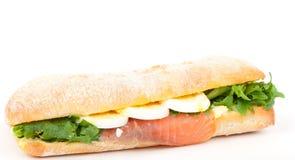 Wirkliches Sandwich mit geräuchertem Lachs, Eiern und Grün auf einem weißen Hintergrund. Stockbild
