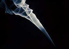 Wirls of a smoky galaxy. A closeup of a backlit smoke creating whirls and curves, isolated on a black background Royalty Free Stock Photo