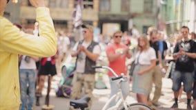 Wirt mit Mikrofon geben Mann in der Sonnenbrille, gewinnenden Kupon der gelben Jacke Leute applaudiert lotterie stock footage