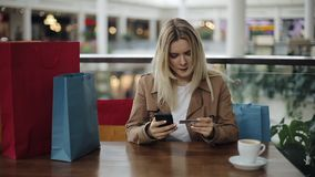 Wirtes della ragazza una serie di carta di credito che si siede con i sacchetti della spesa nel caffè stock footage