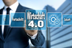 Wirtschaft 4.0 in german economy touchscreen is operated by a. Businessman Stock Images