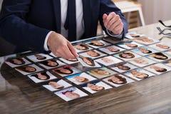 Wirtschaftler-Choosing Fotograf Of-Kandidat lizenzfreies stockbild