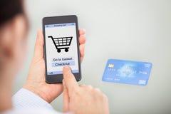 Wirtschaftler, der online mit Handy und Kreditkarte kauft Stockfotos