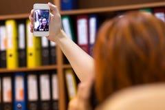Wirtschaftler, der Selbstporträt am Handy am Arbeitsplatz nimmt Lizenzfreie Stockbilder