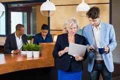 Wirtschaftler, die auf Schreibarbeit im Büro sich besprechen Stockfotos