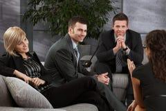 Wirtschaftler, die auf Sofa stillstehen Stockbild