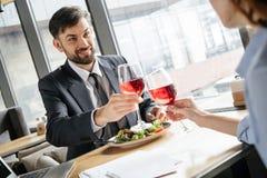 Wirtschaftler, die Business-Lunch am Restaurant sitzt nahe dem trinkenden Weinlächeln des Fensters glücklich zu Mittag essen lizenzfreies stockfoto