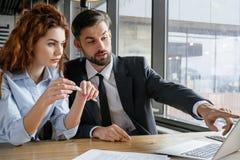 Wirtschaftler, die Business-Lunch am sitzenden Mann des Restaurants stellt die Frauenfrage zeigt auf Laptop zu Mittag essen stockbilder