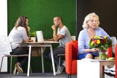 Wirtschaftler, die an der Büro-Lobby sich besprechen Stockfotos