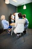 Wirtschaftler, die an der Büro-Lobby sich besprechen Lizenzfreie Stockbilder