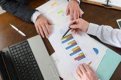 Wirtschaftler, die eine Diskussion über Finanzbericht haben Stockfoto