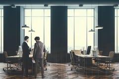 Wirtschaftler, die in einem grauen Büro, getont sprechen Lizenzfreie Stockfotos