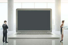 Wirtschaftler, die enormen Laptop betrachten Lizenzfreie Stockbilder
