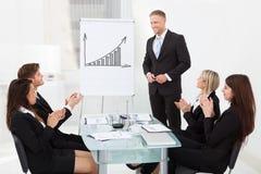Wirtschaftler, die für Kollegen nach Darstellung klatschen Lizenzfreie Stockfotos