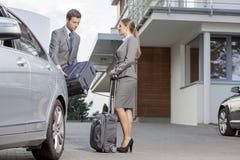Wirtschaftler, die Gepäck vom Auto außerhalb des Hotels entladen Stockfoto