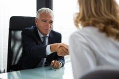 Wirtschaftler, die Hände während einer Sitzung rütteln Lizenzfreie Stockfotografie