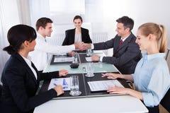 Wirtschaftler, die Hand in der Sitzung rütteln Lizenzfreies Stockfoto