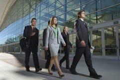 Wirtschaftler, die hinter Bürogebäude gehen Lizenzfreie Stockfotografie
