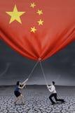 Wirtschaftler, die hinunter eine chinesische Flagge ziehen Lizenzfreie Stockfotos
