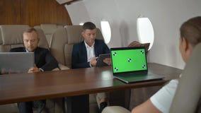 Wirtschaftler, die innerhalb des Flugzeuggeschäftsjets sich besprechen stock video