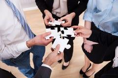 Wirtschaftler, die Puzzlen halten Stockbilder