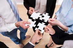 Wirtschaftler, die Puzzlen halten Stockfotografie