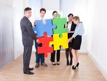 Wirtschaftler, die Puzzlen zusammenbauen Lizenzfreies Stockfoto