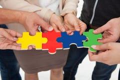 Wirtschaftler, die Puzzlespielstücken sich anschließen Lizenzfreies Stockbild