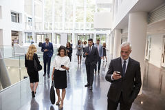 Wirtschaftler, die Technologie im beschäftigten Lobby-Bereich des Büros einsetzen lizenzfreie stockfotos