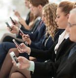 Wirtschaftler, die Technologie im beschäftigten Lobby-Bereich des Büros einsetzen stockfoto