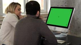 Wirtschaftler, die Tischrechnerinformationen im Büro vergleichend mit-arbeiten Grüne Schirm-Modell-Anzeige stock video footage