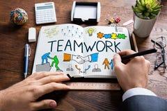 Wirtschaftler Drawing Teamwork Concept auf Notizbuch Stockfotos