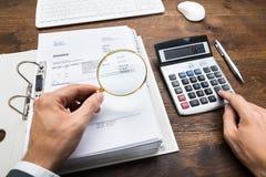 Wirtschaftler-Examining Bills With-Lupe Stockfotografie