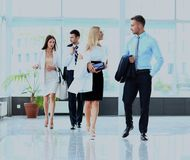 Wirtschaftler gruppieren das Gehen am modernen hellen Büroinnenraum stockfotografie