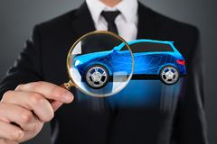 Wirtschaftler Holding Magnifying Glass in Front Of Blue Car stockfotos