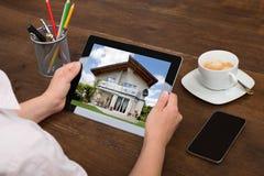 Wirtschaftler-Looking At House-Foto auf Digital-Tablet Lizenzfreies Stockbild