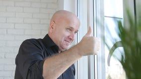 Wirtschaftler Make Victory Sign Thumbs Up Looking glücklich auf dem Fenster lizenzfreie stockfotografie