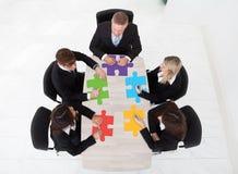 Wirtschaftler mit den zackigen Stücken, die bei Tisch sitzen Lizenzfreies Stockbild