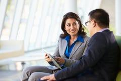 Wirtschaftler mit Digital-Tablette, die im modernen Büro sitzt Stockbild