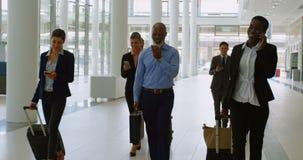 Wirtschaftler mit Koffer unter Verwendung der Handys beim Gehen in Büro 4k stock video