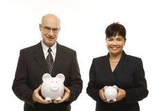 Wirtschaftler mit piggybanks stockfotos
