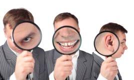 Wirtschaftler mit Vergrößerungsglas auf Ohr, Auge, Mund Lizenzfreies Stockbild