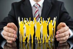 Wirtschaftler-Protecting Paper Cutout-Leute Stockbild