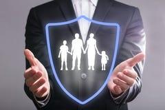 Wirtschaftler ` s Hand mit Schild-schützender Familie stockbild