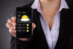 Wirtschaftler Showing Weather Forecast am Handy Stockbild