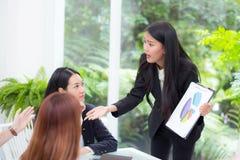 Wirtschaftler, welche die Geschäftsfraumeinung unterschiedlich sein Kollege in der Sitzung betrachten stockfotografie