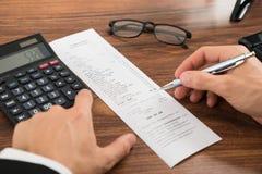 Wirtschaftlerhände, die Ausgaben am Schreibtisch berechnen Lizenzfreies Stockfoto