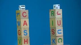 Wirujący dwa alfabetycznej sześcian sterty z słowem Spienięża i Ryzykuje i kostka do gry zdjęcie wideo