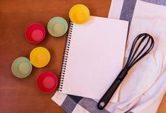 Wischen Sie, backende Schalen des Silikons des kleinen Kuchens und leeres Notizbuch Lizenzfreie Stockbilder